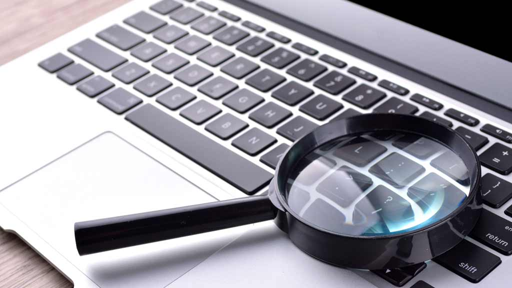 Laptop with a magnifying glass laying on the keyboard