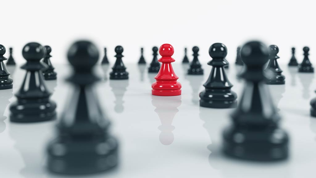 Red chess piece standing out among black chess pieces