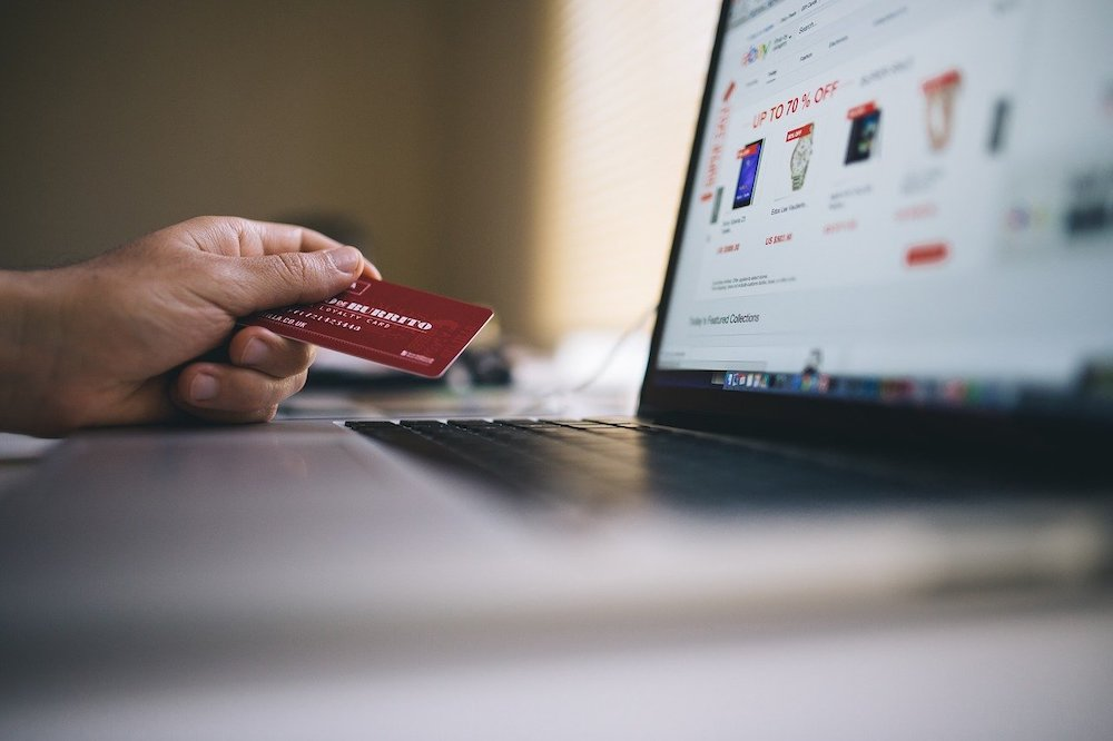 hand holding credit card by laptop before making online purchase