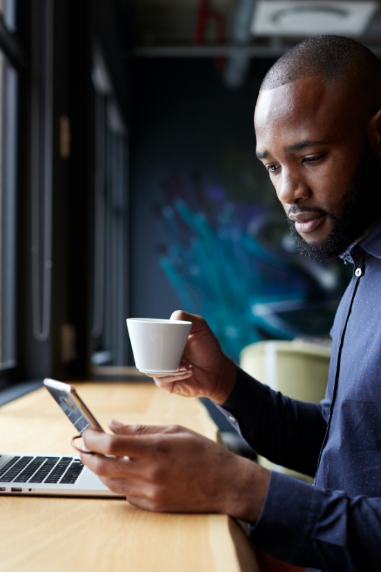 Man holding coffee and smart phone